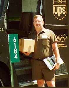 Photograph of a UPS driver standing next to a 911 Sign.